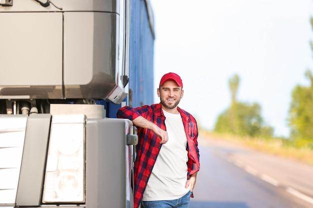 Mannelijke bestuurder in de buurt van grote vrachtwagen buitenshuis