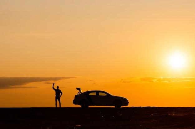 Mannelijke bestuurder opgeheven hand en wacht op hulp, auto kan niet verder rijden na een storing bij zonsondergang