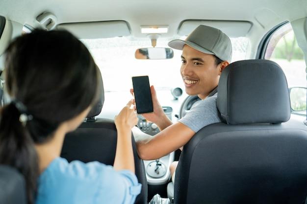 Mannelijke bestuurder toont zijn smartphone om de betaling goed te keuren