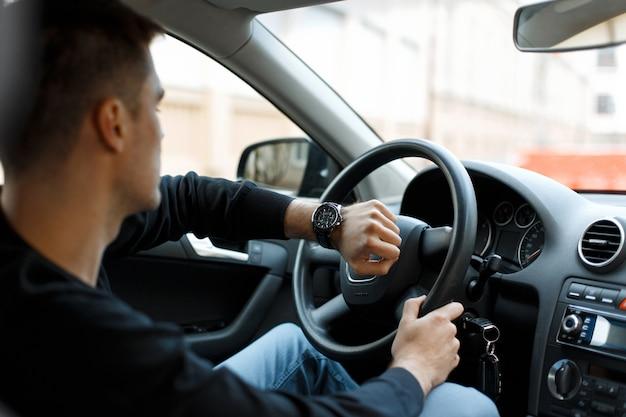 Mannelijke bestuurder zit in de auto in de verkeersopstopping en kijkt naar de klok