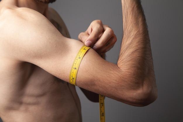 Mannelijke biceps en meetlint