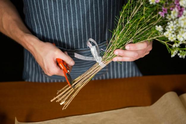 Mannelijke bloemist bloemstengel in bloemenwinkel trimmen