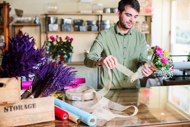 Mannelijke bloemist die boeket in bloemwinkel maken
