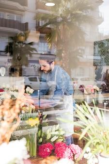 Mannelijke bloemist die de bloemen schikt die door het glas in de bloemwinkel worden gezien