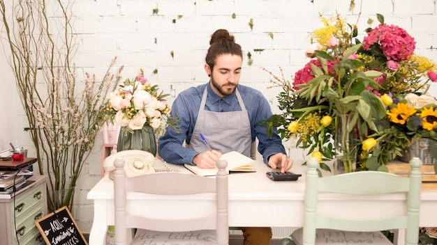 Mannelijke bloemist die de financiën in de bloemwinkel berekenen