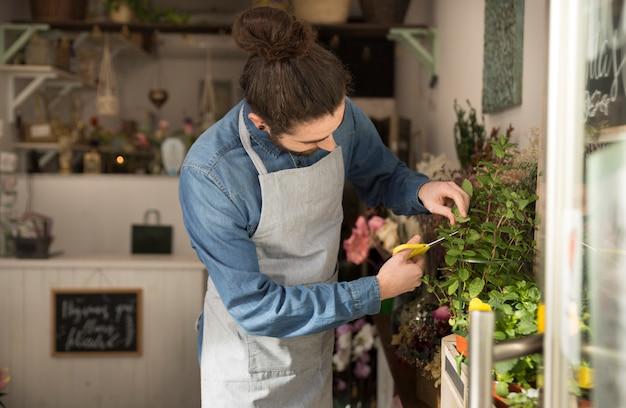Mannelijke bloemist die de installatie in de bloemwinkel snoeit