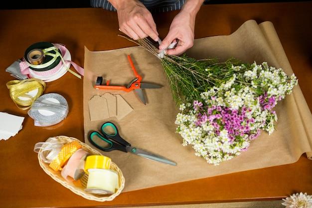 Mannelijke bloemist die een bloemboeket voorbereidt