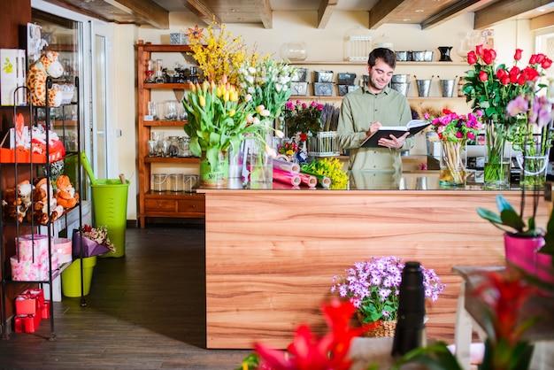 Mannelijke bloemist die nota's in een bloemwinkel neemt