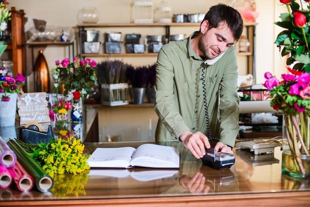 Mannelijke bloemist die orden over een telefoon in een bloemenwinkel goedkeuren