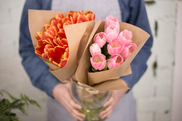 Mannelijke bloemist die roze en een oranje tulpenboeket houdt dat in document wordt verpakt