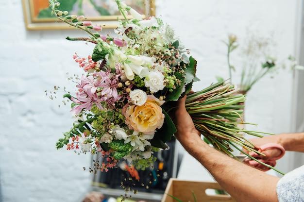 Mannelijke bloemist mooi boeket afwerken