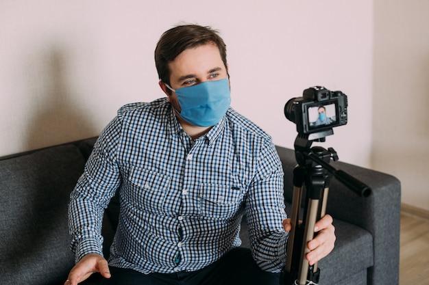Mannelijke blogger die over de pandemie van het coronavirus streamt. blijf thuis voor zelfquarantaine op afstand.