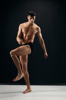Mannelijke bodybuilder met een gespierd lichaam in een donker slipje poseren
