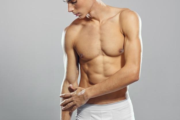 Mannelijke bodybuilder poseren sportschool lichte achtergrond