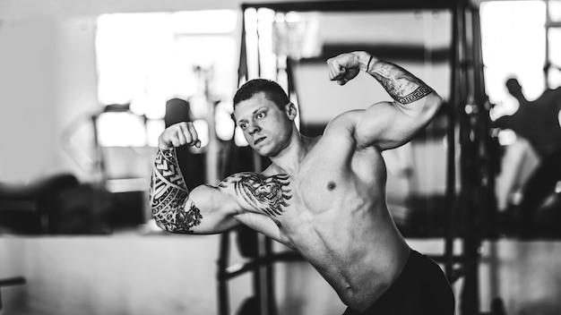 Mannelijke bodybuilder voert oefeningen uit voor een spiegel.