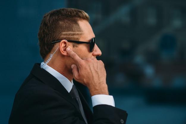 Mannelijke bodyguard praten door oortelefoon buitenshuis, communicatie-instrumenten voor beveiliging.