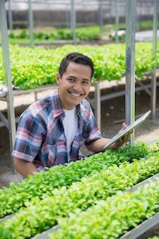 Mannelijke boer in de kas boerderij