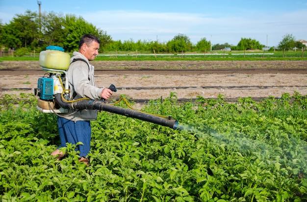 Mannelijke boer met een nevelspuit verwerkt aardappelstruiken met chemicaliën beheersing van het gebruik van chemicaliën