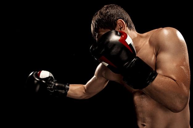 Mannelijke bokser boksen in bokszak met dramatische gespannen verlichting