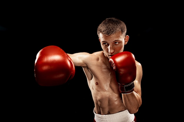 Mannelijke bokser boksen met dramatische edgy verlichting op zwart