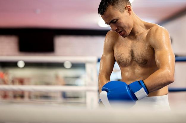 Mannelijke bokser die beschermende handschoenen aanpast