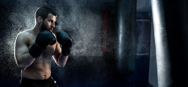 Mannelijke bokser die een enorme bokszak raakt in een boksstudio. man bokser hard trainen. hoge kwaliteit foto
