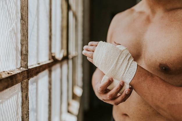 Mannelijke bokser die een riem om zijn hand doet