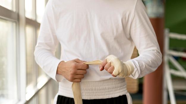 Mannelijke bokser die zijn handen met beschermend koord verpakt