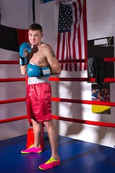 Mannelijke bokser met blote borst in bokshandschoenen die zich dichtbij rode hoek bevinden