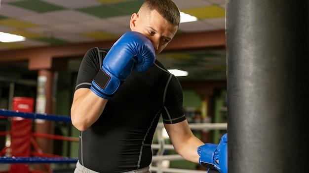 Mannelijke bokser met handschoenen die aan de ring trainen