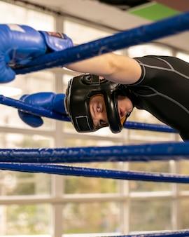 Mannelijke bokser met handschoenen en helm in de ring
