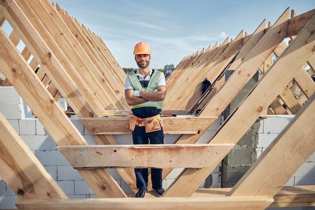 Mannelijke bouwer die er tevreden uitziet en een volledig uniform en uitrusting draagt terwijl hij zijn armen op de borst heeft gekruist
