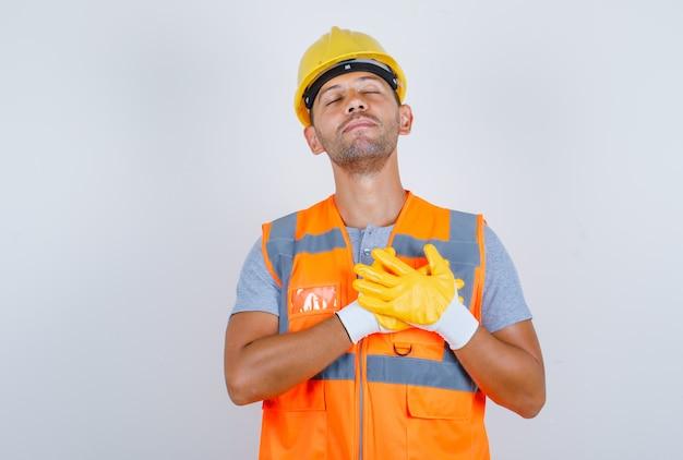 Mannelijke bouwer die handen op hart in uniform, helm, handschoenen houdt en dankbaar, vooraanzicht kijkt