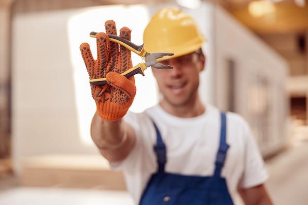 Mannelijke bouwer dient werkhandschoenen in met een tang