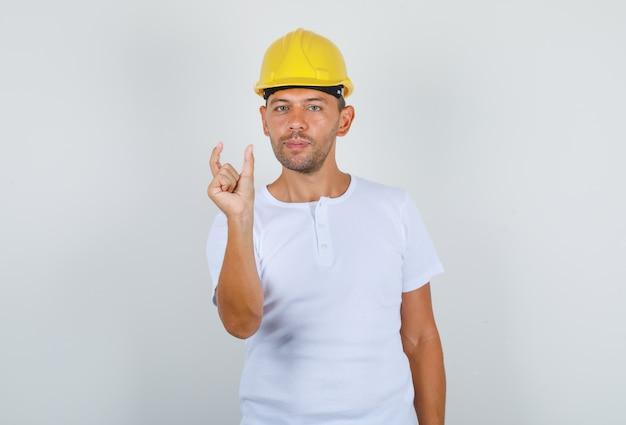 Mannelijke bouwer doet klein formaat bord met vingers in wit t-shirt, veiligheidshelm vooraanzicht.