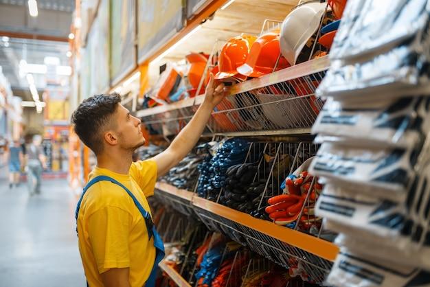 Mannelijke bouwer helm kiezen op de plank in ijzerhandel. constructeur in uniform bekijkt de goederen in de doe-het-zelfwinkel