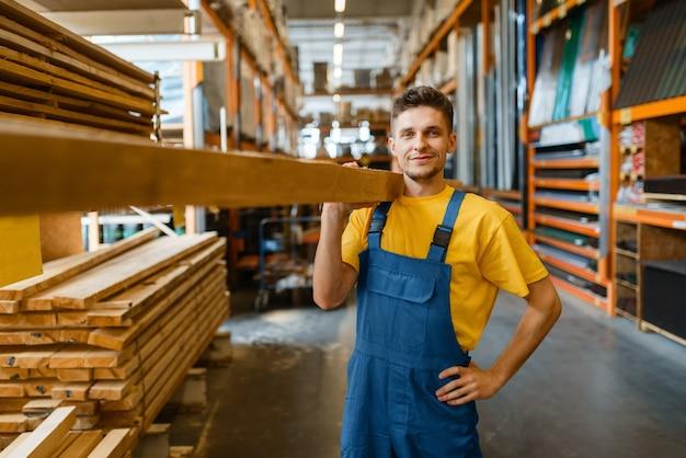 Mannelijke bouwer houdt houten planken in ijzerhandel. de klant bekijkt de goederen in de doe-het-zelfwinkel