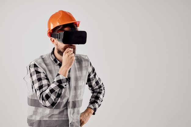 Mannelijke bouwer in een oranje professionele lichte achtergrond van helmtechnologie
