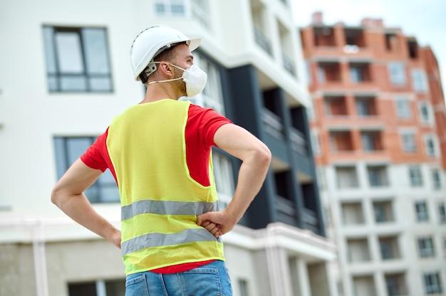 Mannelijke bouwer in een veiligheidsvest wegkijkend