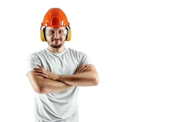 Mannelijke bouwer in oranje helm die op witte achtergrond wordt geïsoleerd