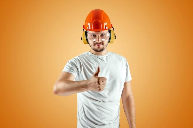 Mannelijke bouwer in oranje helm op een oranje achtergrond