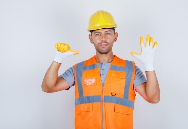 Mannelijke bouwer in uniform, helm, handschoenen die nummer zes met vingers, vooraanzicht tonen.