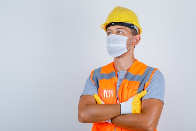 Mannelijke bouwer in uniform, helm, handschoenen, masker wegkijken met gekruiste armen en voorzichtig, vooraanzicht kijken.