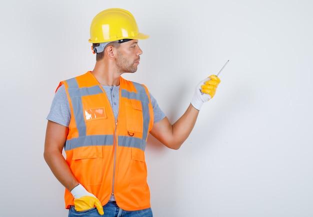 Mannelijke bouwer in uniform, jeans, helm, handschoenen met schroevendraaier met hand in zak, vooraanzicht.