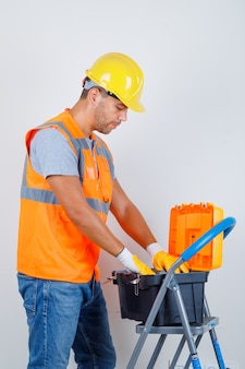 Mannelijke bouwer in uniform, jeans, helm, handschoenen op zoek naar iets in de gereedschapskist.