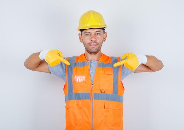 Mannelijke bouwer in uniform toont zichzelf met wijsvingers en kijkt zelfverzekerd, vooraanzicht.