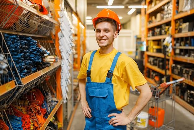 Mannelijke bouwer probeert op helm op de plank in ijzerhandel. constructeur in uniform bekijkt de goederen in de doe-het-zelfwinkel