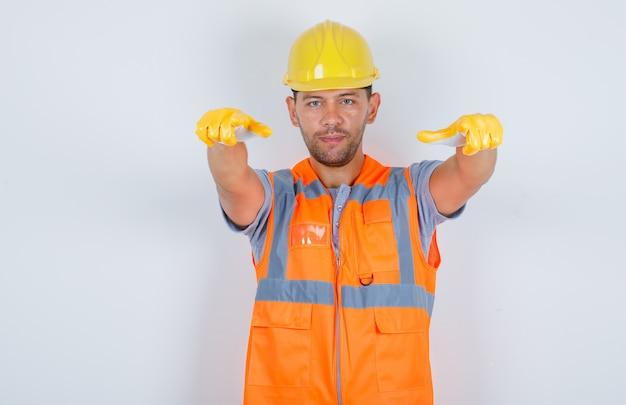 Mannelijke bouwer wijzen en kijken naar camera in uniform, helm, handschoenen vooraanzicht.