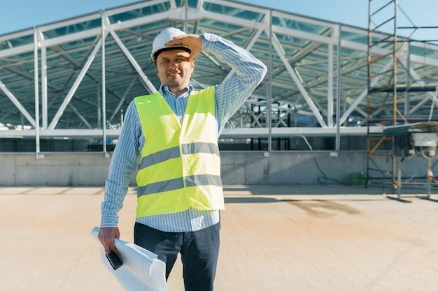 Mannelijke bouwinspecteur die bouwwerf onderzoeken