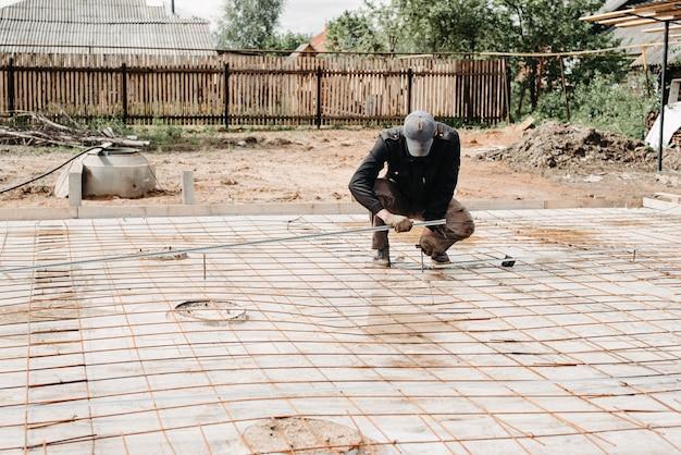 Mannelijke bouwvakker bereidt wapening voor voor de fundering van de bouw van het huis en het storten van beton